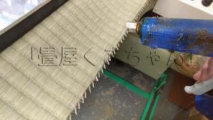 畳表のイグサが解れないように「経糸」を畳用ホットメルトで固定します。 無農薬畳表の場合は手作業で括り縛ります。